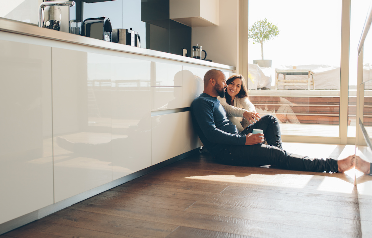Young Man And Woman Sitting On Luxury Vinyl Tile Floor In Kitchen And Talking.